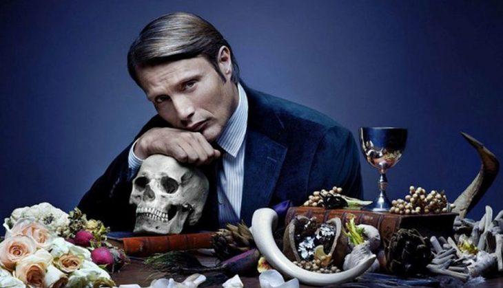 Hombre sentado a la mesa recargado en un cráneo, escena de la serie Hannibal