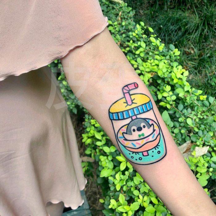 Tatuajes tiernos de Pikka Cool Cool Tattoo; tatuaje kawaii de pinguino sobre una dona en un termo con agua
