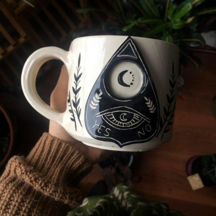 Taza de caldero de bruja, blanca con puntero de ouija con un ojo y luna negra