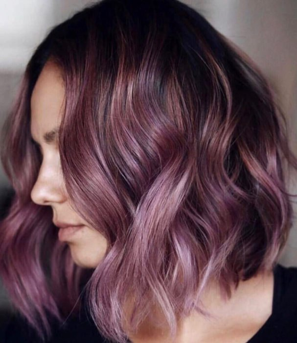 Tinte color chocolate lila; chica con cabello castaño morado, corto ondulado