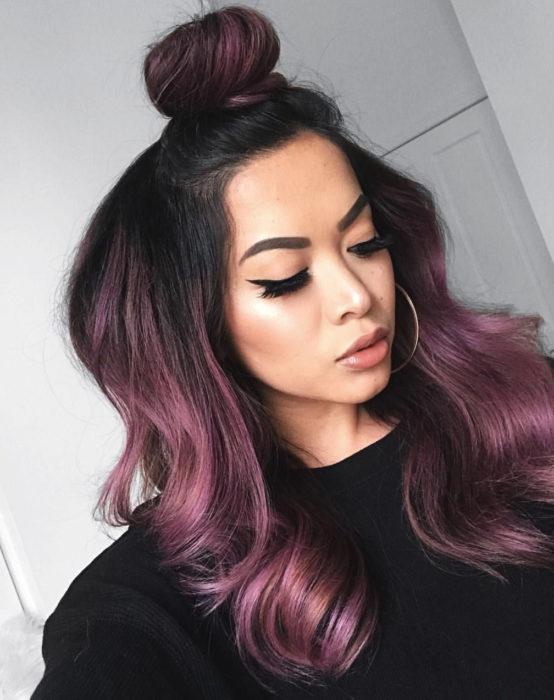 Tinte color chocolate lila; chica con cabello castaño morado, largo, ondulado y con peinado de medio chongo alto