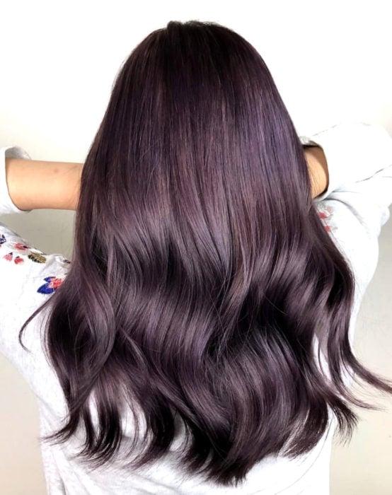 Tinte color chocolate lila; chica con cabello castaño morado, largo y lacio, ondulado de las puntas