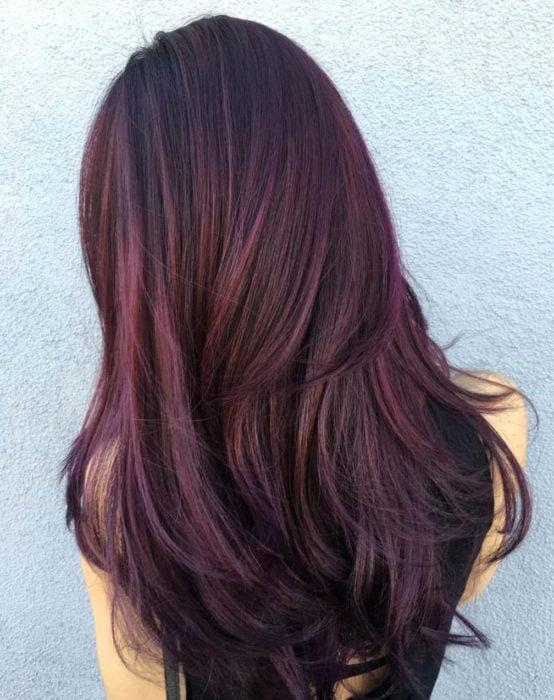 Tinte color chocolate lila; chica con cabello castaño morado largo y lacio, peinado con secadora