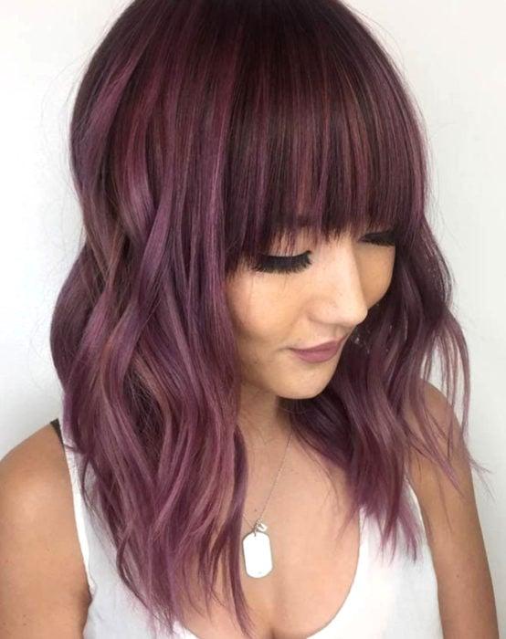 Tinte color chocolate lila; chica con cabello castaño morado, abajo de los hombros, con fleco