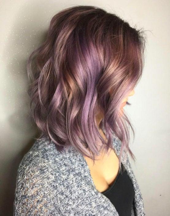 Tinte color chocolate lila; chica con cabello castaño con luces moradas, corto arriba del hombro, ondulado