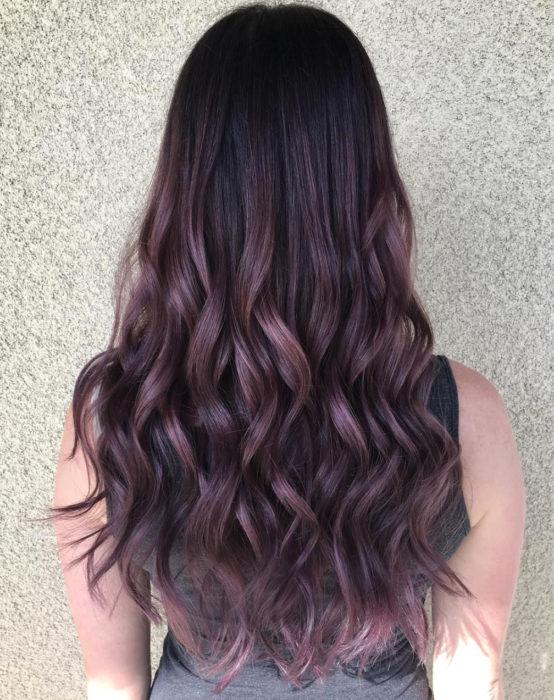 Tinte color chocolate lila; chica con cabello castaño morado, largo y ondulado