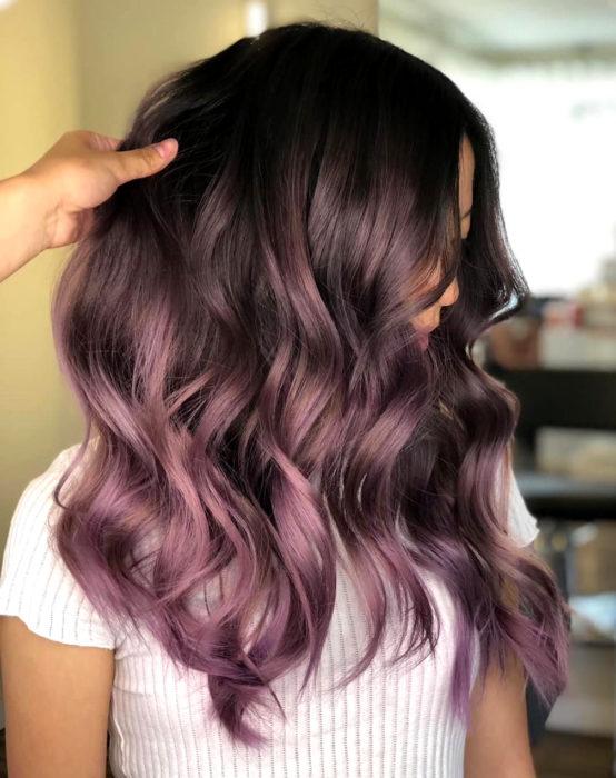 Tinte color chocolate lila; chica con cabello castaño morado, ondulado y largo