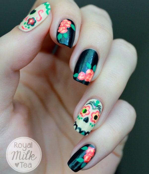 Manicura de Día de Muertos; uñas largas y cuadradas, pintadas con esmalte negro con calaveras y flores