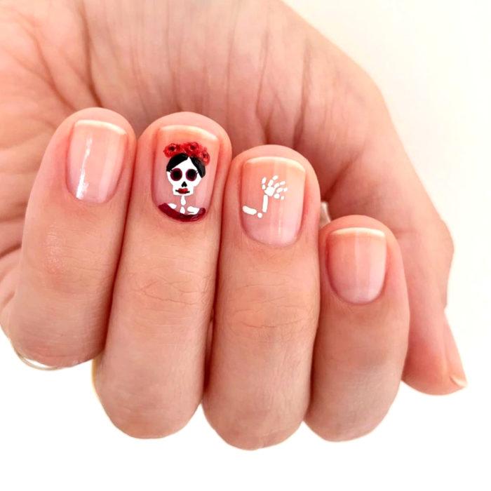 Manicura de Día de Muertos; uñas cortas con esmalte transparente con diseño de catrina