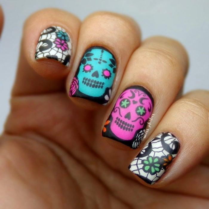 Manicura de Día de Muertos; uñas cortas cuadradas pintadas de negro con diseño de calaveras y flores de papel picado