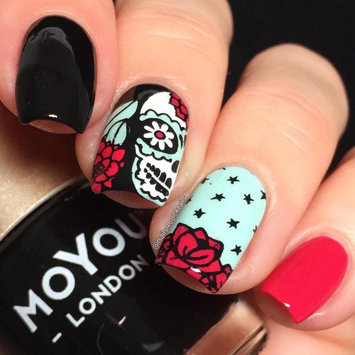 Manicura de Día de Muertos; uñas largas cuadradas pintadas con esmalte negro, azul y rojo con diseño de calaveras de dulce con flores