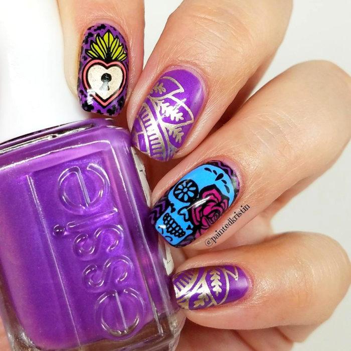 Manicura de Día de Muertos; uñas largas cuadradas pintadas con esmalte morado con diseño de cráneo, con flores y corazón