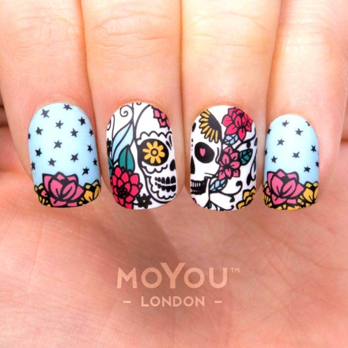 Manicura de Día de Muertos; uñas largas cuadradas pintadas con esmalte azul cielo con diseño de cráneos con flores amarillas, rojas y rosas, con estrellas