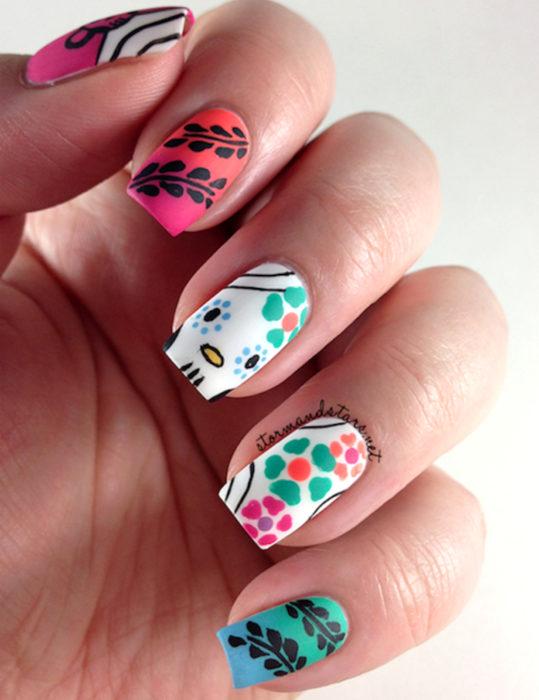 Manicura de Día de Muertos; uñas largas pintadas de rosa y azul con degradado anaranjado y verde, con diseño de calavera con flores
