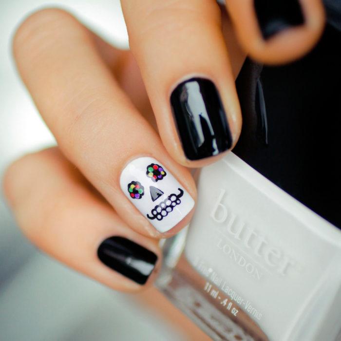 Manicura de Día de Muertos; uñas cortas cuadradas pintadas de negro y una uña con diseño de cráneo con flores en los ojos