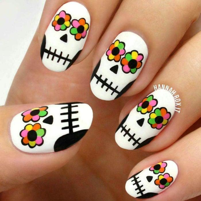 Manicura de Día de Muertos; uñas en forma de almendra pintadas con calaveras de dulce con ojos de flores de altar