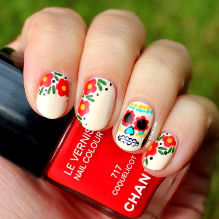 Manicura de Día de Muertos; uñas cortas pintadas con esmalte blanco con calavera de dulce y flores rojas