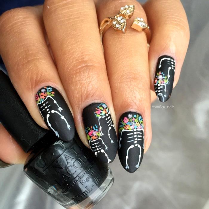 Manicura de Día de Muertos; uñas largas en forma de almendra pintadas de color negro con calaveras y flores de colores rosas, azules, amarillas, moradas y moradas