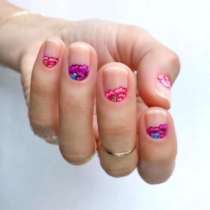 Manicura de Día de Muertos; uñas cortas pintadas con esmalte transparente y flores de altar de color rosa y morado