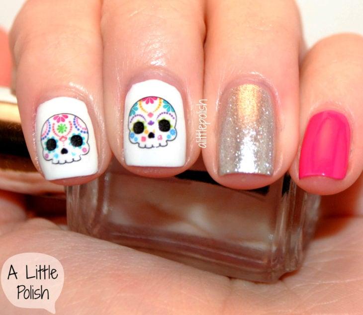 Manicura de Día de Muertos; uñas pintadas diferente, con esmalte blanco, plateado con glitter y rosa, con diseño de calavera de dulce con flores