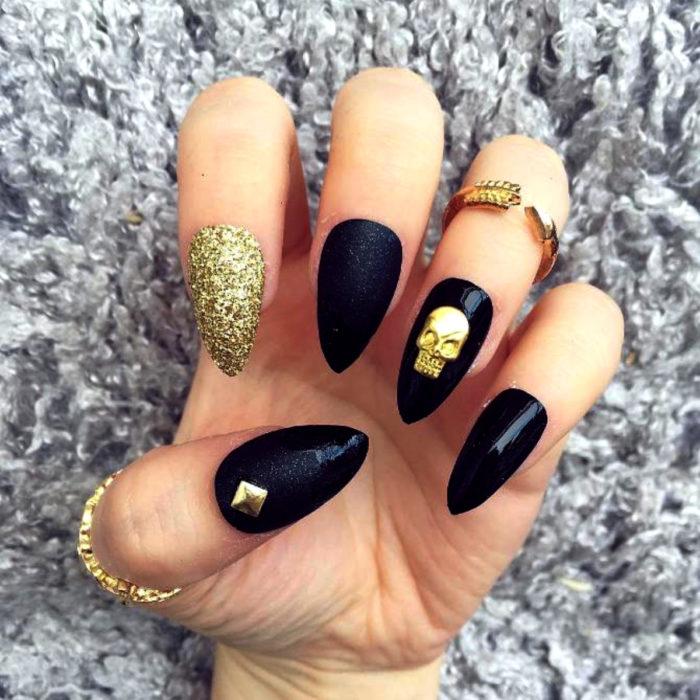 Manicura de Día de Muertos; uñas largas en forma de almendra, pintadas diferente con esmalte negro y dorado con glitter, y con adorno de cráneo y un estoperol