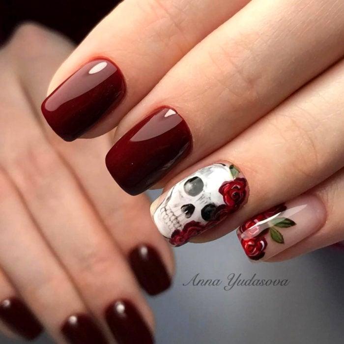 Manicura de Día de Muertos; uñas largas cuadradas, pintadas con esmalte color rojo vino y diseño de cráneo con flores