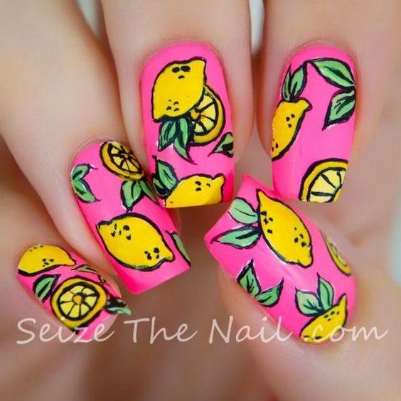 Manos de una chica con diseño de uñas pop art con estampados de limones y el fondo de color rosa