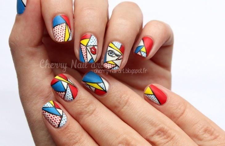 Manos de una chica con diseño de uñas pop art en color blanco con viñetas