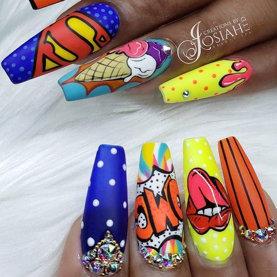 Manos de una chica con diseño de uñas pop art en colores con viñetas de superhéroes de cómics