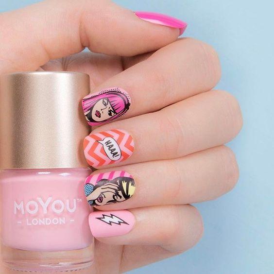 Manos de una chica con diseño de uñas pop art en color rosa con etiquetas