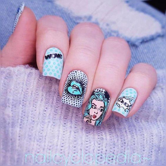 Manos de una chica con diseño de uñas pop art en color azul con viñetas de cómic