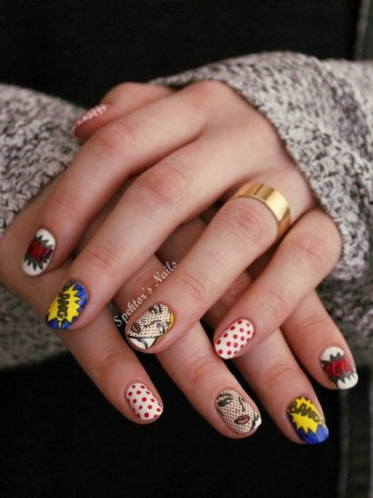 Manos de una chica con diseño de uñas pop art en color blanco con viñetas de cómics