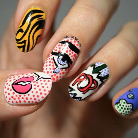 Manos de una chica con diseño de uñas pop art en colores con diferentes colores