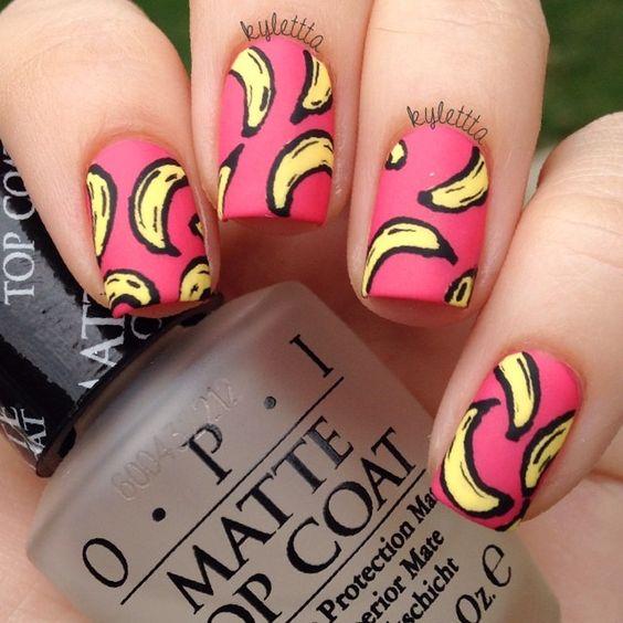 Manos de una chica con diseño de uñas pop art en color rosa con plátanos dibujados