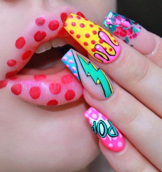 Manos de una chica con diseño de uñas pop art en colores amarillo, rosa y azul