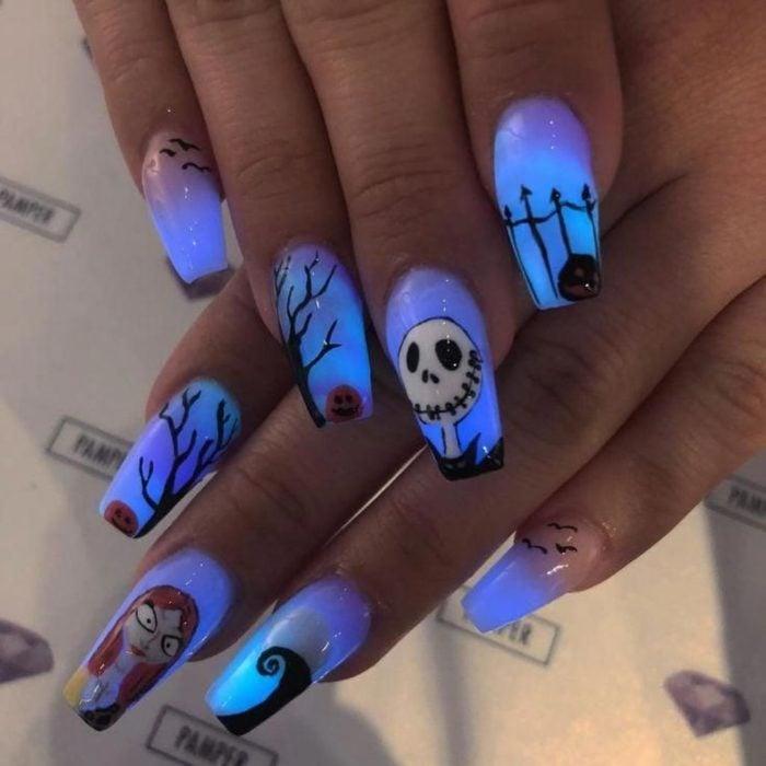 Chica usando unas uñas de color azul neón con los personajes de jack de la película pesadilla antes de Navidad