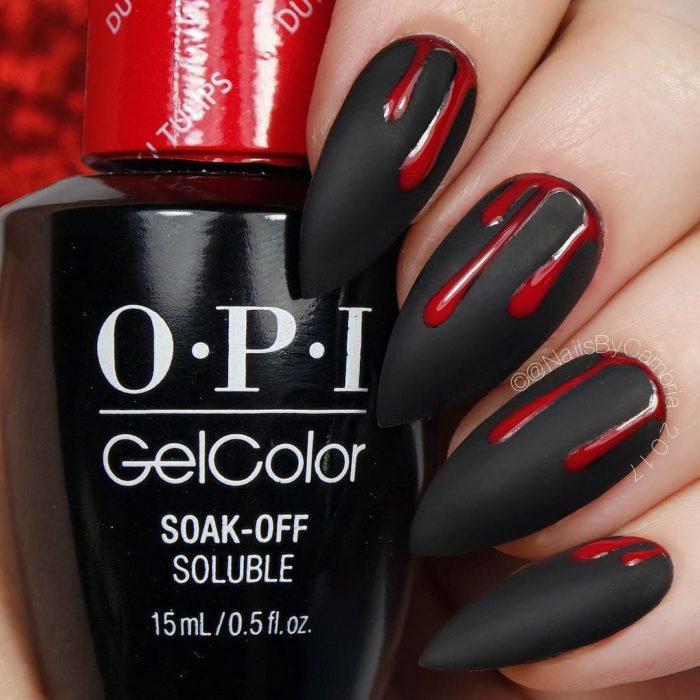 Chica con unas uñas en forma de almendra y de color negro con diseños estilo sangre de color rojo