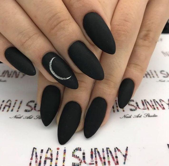 Uñas en forma de almendra en color negro mate con una luna pintada