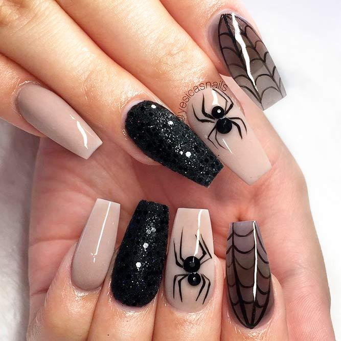 Chica con un diseño de uñas en color nude con negro y telarañas y arañas pintadas