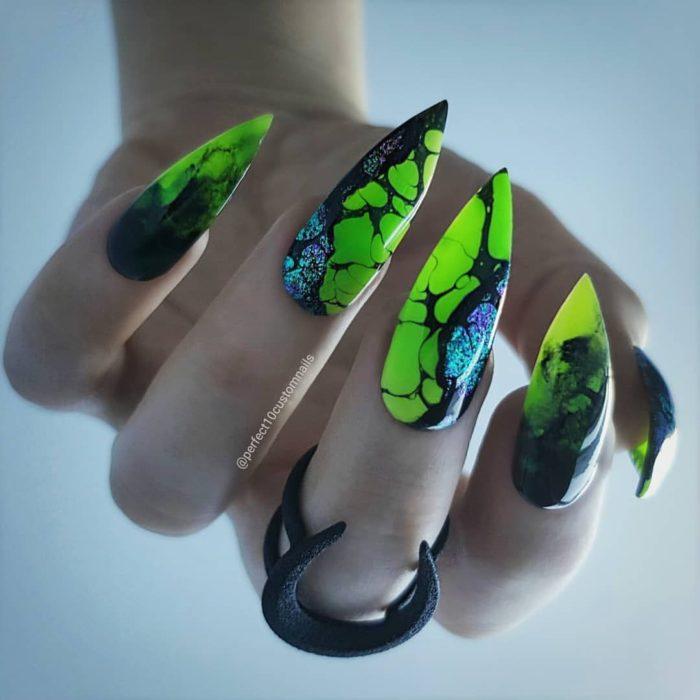Chica con unas uñas en forma de almendra en color neón con diseños negros