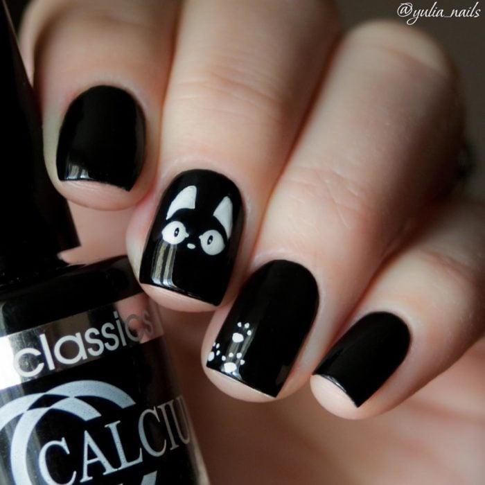 Chica con las uñas pintadas de color negro con un gato de color blanco