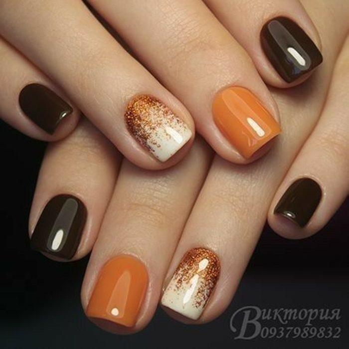 chica con las uñas pintadas de color café con naranja perfectas para Halloween