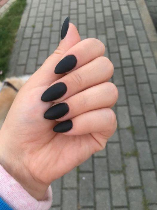 Chica mostrando sus uñas de color totalmente negro