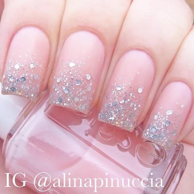 Chica sosteniendo en sus manos un tono de uñas color rosa con glitter