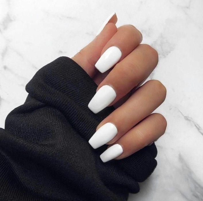 Chica mostrando sus uñas de color blanco