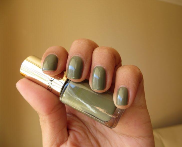Chica sosteniendo un esmalte de color verde olivo mientras enseña sus uñas del mismo tono