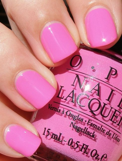 Chica usando unas uñas de color rosa barbie mientras enseña el esmalte del mismo color