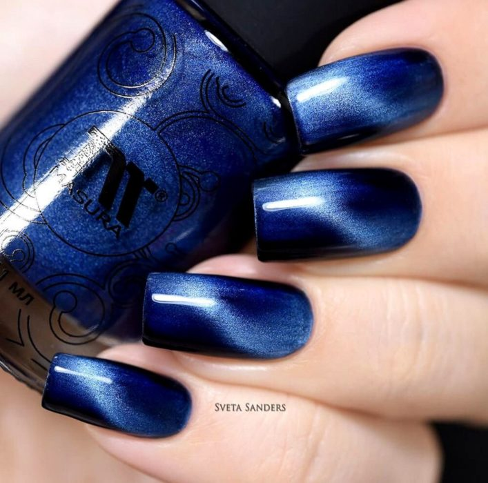 Chica mostrando las uñas azul cobalto mientras sostiene un esmalte