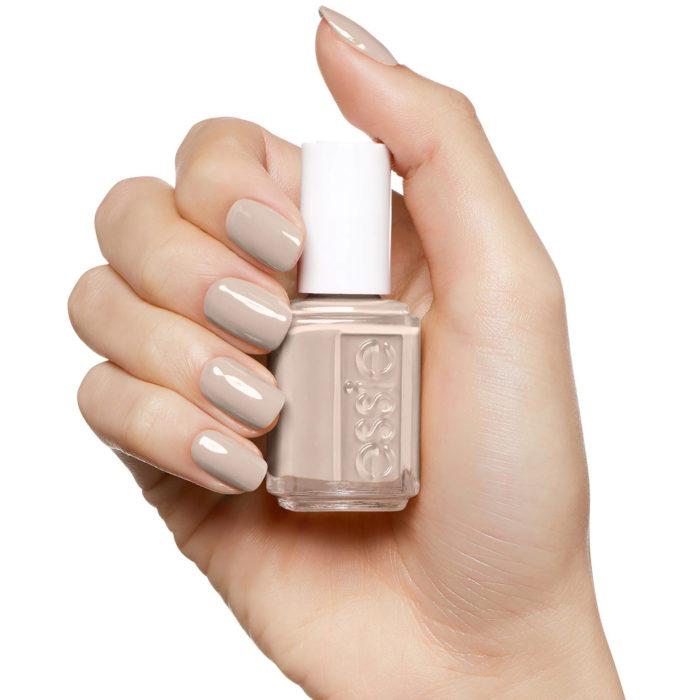 Chica con las uñas de color arena sosteniendo el esmalte del tono