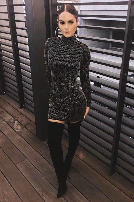 Mujer con vestido ceñido, color negro con mangas y botas largas arriba de la rodilla